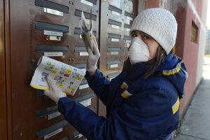 Poštová doručovateľka roznáša zásielky v gumených rukaviciach a s ochranou nosa i úst v Košiciach 13. marca 2020.