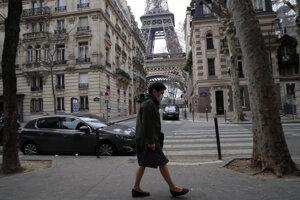 Žena s ochranným rúškom kráča cez prázdne ulice neďaleko Eiffelovej veži v Paríži.