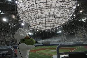 Zamestnanec v ochrannom odeve dezinfikuje vnútorné priestory na bejzbalovom štadióne Gocheok Sky Dome v juhokórejskom Soule. Kórejská bejzbalová organizácia odložila štart novej sezóny kvôli koronavírusu.