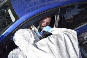 Pracovník v ochrannom obleku odoberá vzorky posádke vozidla na drive-thru test na nový koronavírus 18. marca 2020 v Bratislave.