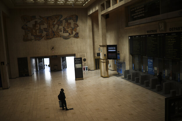 Muž sa pozerá na tabuľu s odchodmi vlakov na prázdnej železničnej stanici z dôvodu šíriaceho sa koronavírusu v Bruseli.
