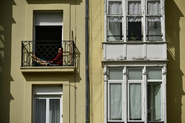 Žena sa slní na balkóne počas karantény proti šíreniu nového typu koronavírusu v severošpanielskom meste Vitória.