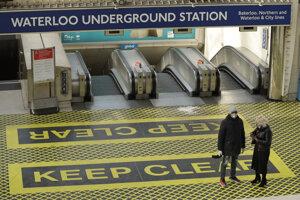 Dvaja ľudia s ochrannými rúškami stoja pri pohyblivých schodoch na stanici metra Waterloo v Londýne.