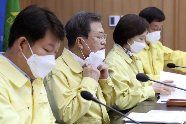 Juhokórejský prezident Mun Če-in (druhý zľava) si dáva ochranné rúško dole z tváre počas mimoriadneho zasadnutia vlády.