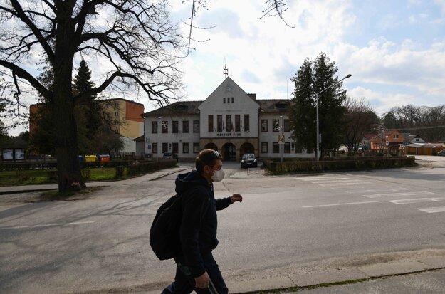 Muž v maske prechádza ulicou pred Mestským úradom v Starej Turej počas mimoriadnej situácie.
