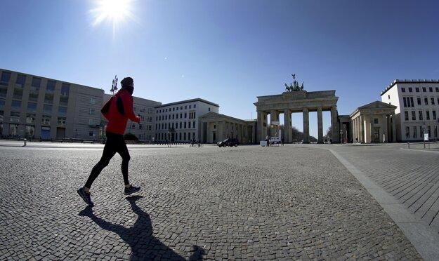 Osamelý bežec na prázdnom námestí pred Brandenburskou bránou v Berlíne.