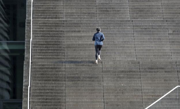 Žena behá po schodoch pred budovou parlamentu vo vládnej štvrti v Berlíne.