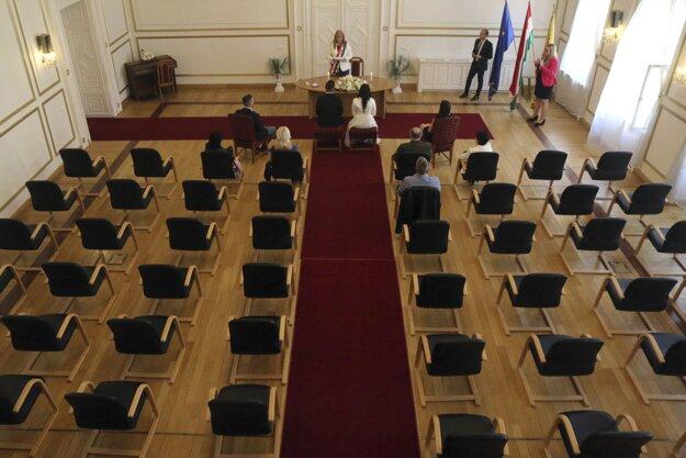 Nevesta a ženích s rodinnými príslušníkmi počas svadobného obradu na radnici v maďarskom Miškovci.