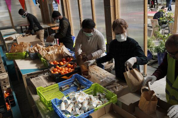 Dobrovoľníci pripravujú potravinové balíčky.