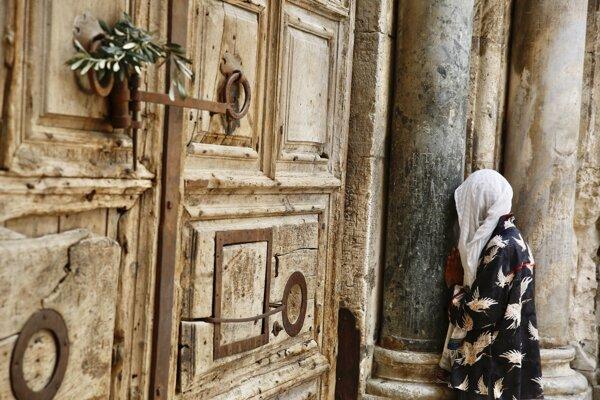 Žena sa modlí pred zavretou bazilikou Božieho hrobu v Jeruzaleme.