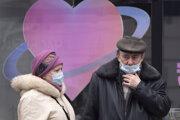 Ľudia s ochrannými rúškami stoja na autobusovej zastávke v Petrohrade.