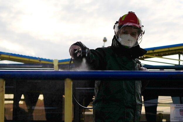 Člen Dobrovoľného hasičského zboru v Kežmarku dezinfikuje špeciálnym prípravkom zábradlie na autobusovej stanici v Kežmarku.
