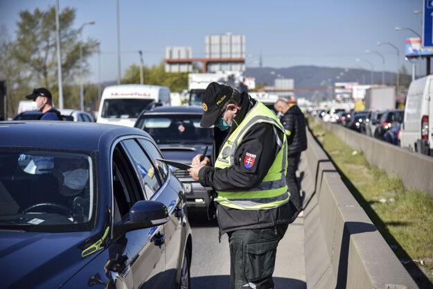 Policajti kontrolujú voličov.