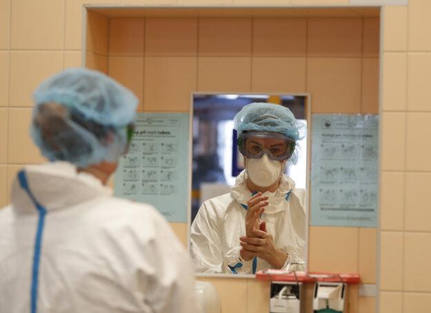 Zdravotná pracovníčka si umýva ruky na jednotke intenzívnej starostlivosti v pražskej univerzitnej nemocnici, v ktorej liečia pacientov s ochorením COVID-19.