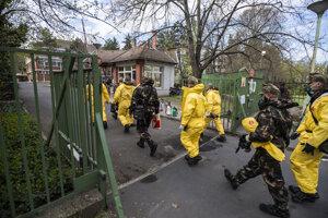 Vojaci v ochranných odevoch prichádzajú kvôli koronavírusu dezinfikovať jeden z domovov dôchodcov v Budapešti.