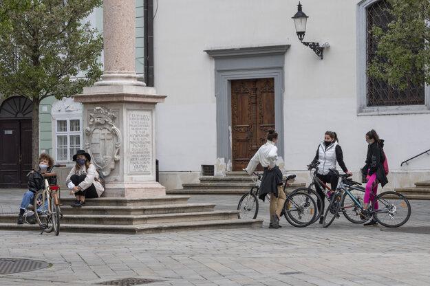 Cyklistky s ochrannými rúškami sa rozprávajú na Františkánskom námestí.