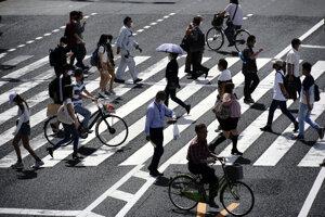 Ľudia prechádzajú cez ulicu v japonskom Tokiu.
