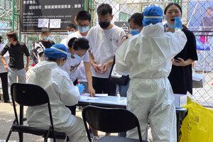 Ľudia čakajú v rade na test na nový druh koronavírusu pred športovým strediskom v Pekingu.