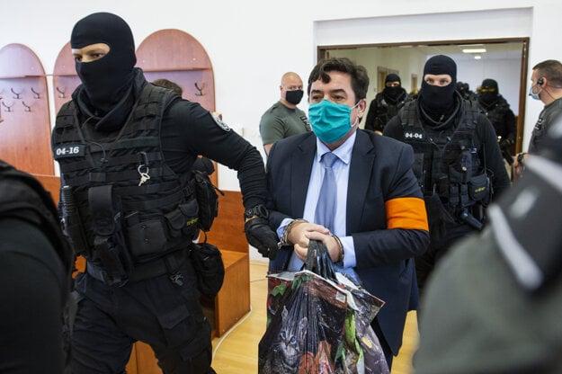 Mariana Kočnera privádzajú do pojednávacej miestnosti.
