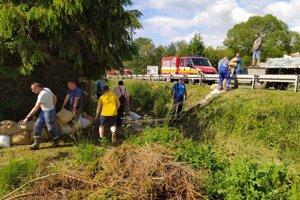 Vrecia naplnené posypovým materiálom sa umiestnili pred ploty pozemkov, ktoré sú priamo ohrozované vodou.pritekajúcou od cesty.