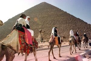 Turisti sa vezú na ťavách pred Veľkou pyramídou, nazývanou aj Cheopsovou.
