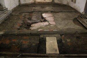Situácia v kaplnke sv. Anny (pôvodnom gotickom presbytériu). Situácia po začistení Vpravo gotický náhrobok Egídia z Bergu? Záver 15. stor. zač.16. stor. a vľavo mladší hrob neznámeho jedinca z cca 17. stor. dlažbou z hlinených dlaždíc.