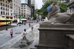 Ikonická socha leva s ochranným rúškom pred knižnicou v New Yorku.