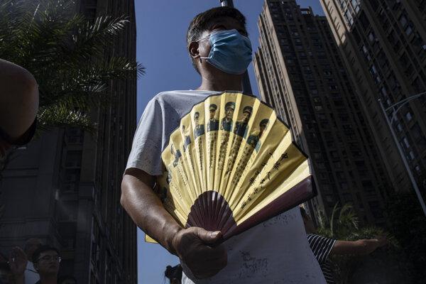 Muž s vejárom zobrazujúcim čínskych generálov počas prípravy čínskych úradov na vstup do amerického konzulátu v meste Čcheng-tu 27. júla 2020.