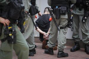 Policajti zatkli demonštranta, ktorého tvár zasiahol paprikový sprej počas protestu v Hongkongu.