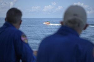 Členovia záchranného tímu Shane Kimbrough (vľavo) a Pat Forrester sa pozerajú na odchádzajúci rýchlostný čln.