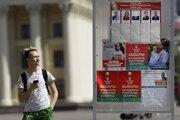 Muž si pozerá plagáty s prezidentskými kandidátmi, pričom tvár bieloruského prezidenta Alexandra Lukašenka je zatretá bielou farbou, pred nedeľnými prezidentskými voľbami 4. augusta 2020 v Minsku.