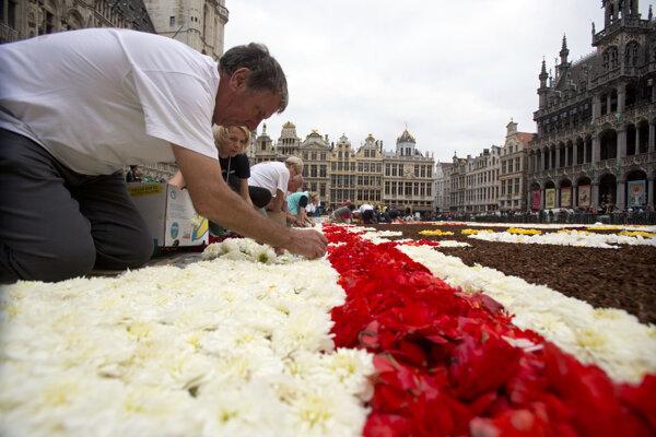 Pokladanie kvetov počas vytvorenia kvetinového koberca na bruselskom námestí Grand Place 16. augusta 2018.