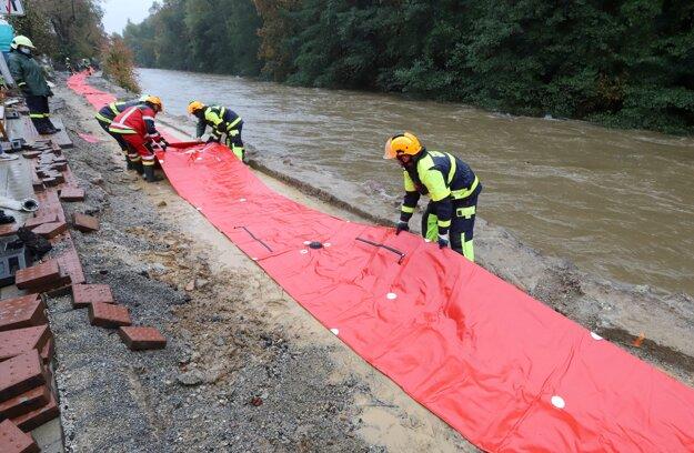 Hasiči stavajú protipovodňové zábrany na brehu riery Hron v Banskej Bystrici.