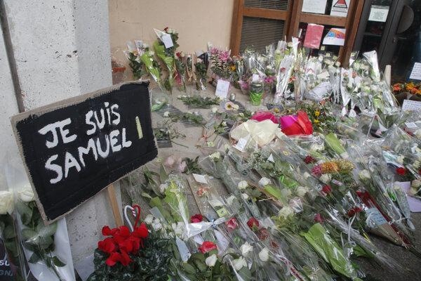Nápis Som Samuel a kvety pred budovou strednej školy, pred ktorou útočník zabil učiteľa dejepisu Samuela Patyho vo francúzskom meste Conflans-Sainte-Honorine v sobotu 17. októbra 2020.