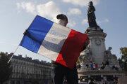 Protestujúci drží francúzsku vlajku s nápisom Sloboda slova počas demonštrácie 18. októbra 2020 v Paríži.