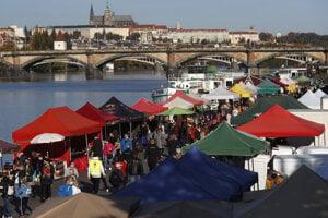 Ľudia si prezerajú stánky na trhu pri rieke Vltava v Prahe v sobotu 24. októbra 2020.