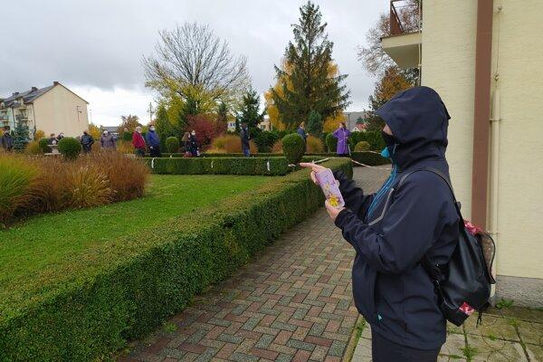 Dobrovoľníci s mobilom v ruke počítajú, koľko ľudí čaká v rade na testovanie.