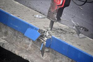 Bagre postupne zbíjačkou drvia betón spadnutého mosta.