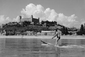Počiatky vodného lyžovania (1955): Netypický záber na Bratislavský hrad z petržalskej strany Dunaja. Hlavným hrdinom tu nie je táto dominanta, ale roztopašný mladý športovec, ktorý namiesto vtedy u nás nedostupných vodných lyží vynaliezavo použil krídlo starých dverí.