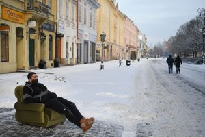 Muž sedí v kresle na zasneženej Hlavnej ulici v Košiciach.