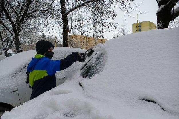 Chlapec odhŕňa sneh z auta na žilinskom sídlisku Vlčince.