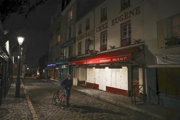 Muž tlačí bicykel v parížskej štvrti Montmartre.