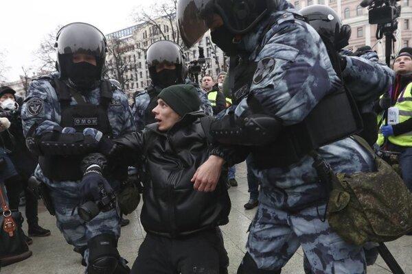 Policajti zatýkajú muža počas protestu.