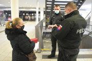 Policajti kontrolujú dodržiavanie protipandemických opatrení na železničnej stanici v Košiciach.