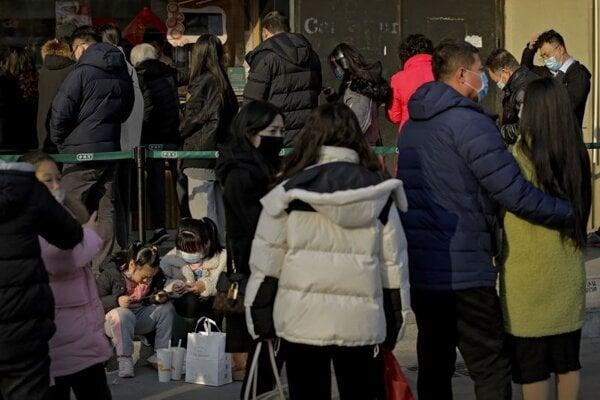 Deti s ochrannými rúškami sa hrajú s hračkou pred obchodom v Pekingu v utorok 9. februára 2021. Počet registrovaných pôrodov v Číne poklesol v roku 2020 o takmer tretinu voči celkovému počtu narodení hlásených rok predtým.