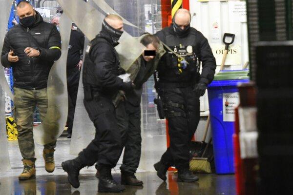 Polícia odvádza páchateľa, zranenú rukojemníčku previezli do nemocnice.