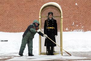 Pracovník samosprávy odpratáva sneh pred príslušníkom čestnej stráže stráže pri Hrobe neznámeho vojaka v Moskve.