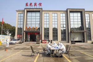 Pracovníci vochranných odevoch sedia pred hotelom, ktorý slúžil na izoláciu ľudí včínskom Wu-chane.