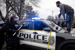 Muž stojí na policajnom aute počas protestu v meste Brooklyn Center.
