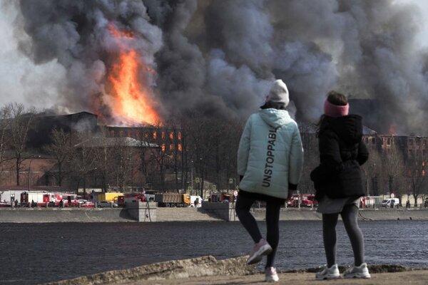 Ľudia sa pozerajú na stúpajúci dym a plamene z horiacej budovy textilnej fabriky Nevskaja Manufaktura v Petrohrade 12. apríla 2021. Požiar zasiahol niekoľko poschodí  budovy fabriky pri brehu rieky Neva.